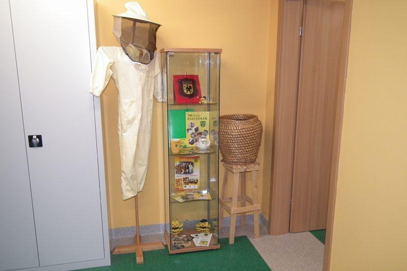 zdjęcie szafa, strój pszczelarza, ekspozytor, stołek z koszem wiklinowym