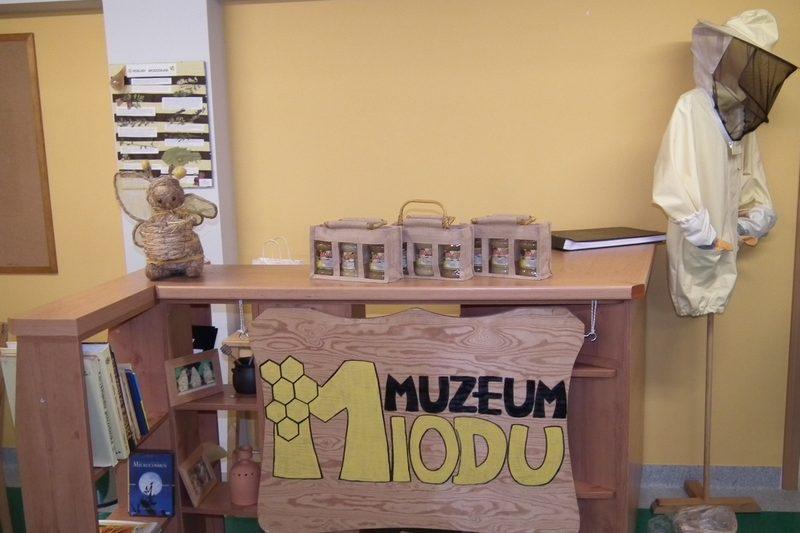 zdjęcie, recepcja muzuem miodu z drewnianym logo, pszczołą zrobioną z sznurka, kombinezon pszczelarza