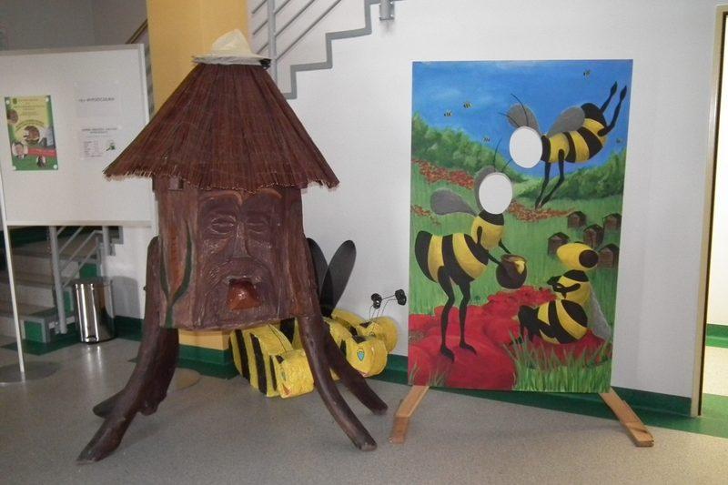 zdjęcie drewniany ul oraz monidło z rysunkiem pszczół
