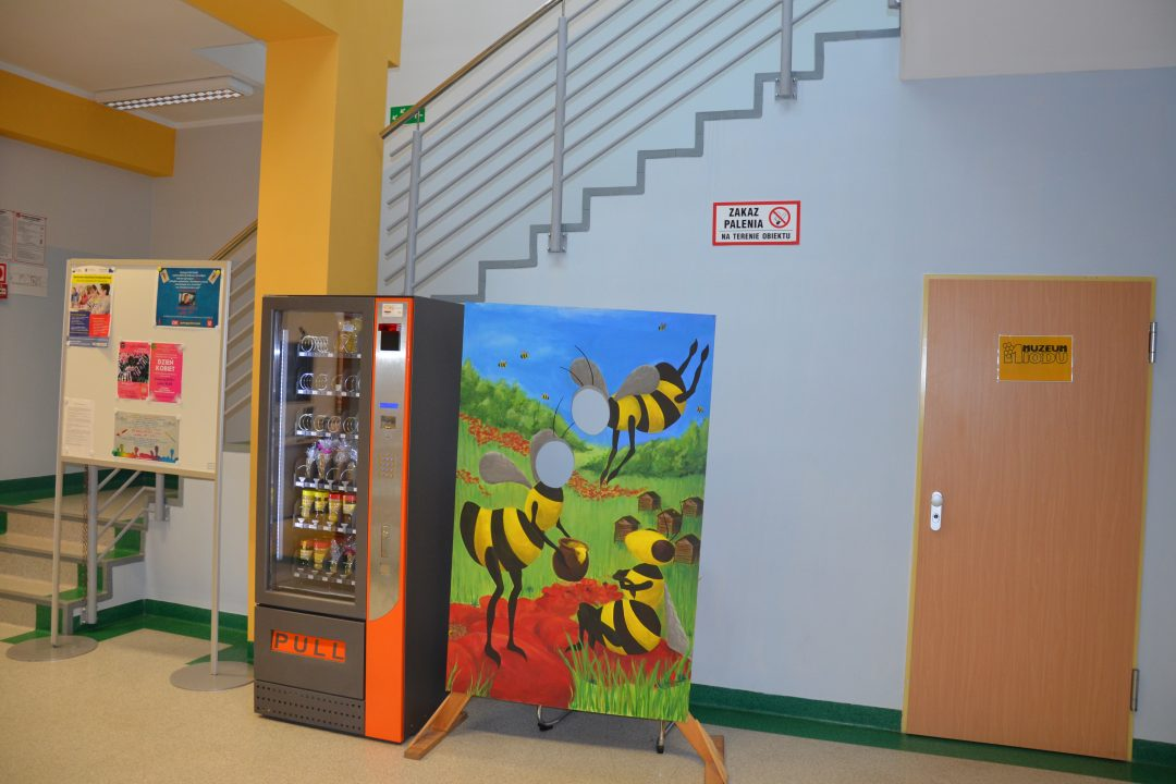 zdjęcie. korytarz biblioteki. od lewej tablica ogłoszeń, automat z przekąskami, monidło z pszczołami, drzwi do muzeum miodu.