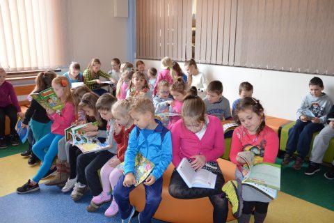 zdjęcie. dzieci siedzą na pufach i czytają książki